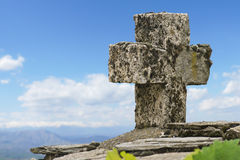 Stone cross at a mountain peak. High in the clouds stock photography