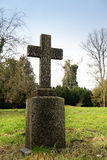 Stone cross in an old park or gravestone in a cemetery, memorial Royalty Free Stock Photography