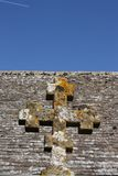 A Stone Cross. An old stone cross seen against the stone tiled roof of a church. Above the roof is a clear, blue sky. The vapour trail of an aircraft is visible Royalty Free Stock Image