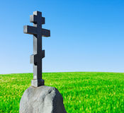 Stone cross on a pedestal stands in a field Stock Photography