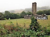 Stone cross sits in a fog-covered pasteur along the Camino de Santiago in Spain. Stock Photos