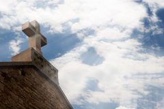 Stone cross in sunlight. A Christian stone cross on the roof and the light from the sky Conceptual image of a Christian spirituality royalty free stock photography