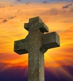 Stone cross. On sunset sky background Stock Images