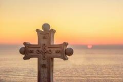 Stone cross with symbols on it on sundown Royalty Free Stock Photo