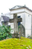 Stone cross on a tomb. A stone cross on an old tomb covered with moss on the Pere Lachaise Cemetery in downtown Paris, France Royalty Free Stock Photos