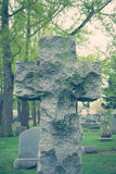 Stone Cross Tombstone. A stone cross tombstone with moss covering it in an old cemetery Stock Photography