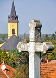 Stone cross and the tower of a church Stock Photo