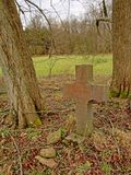 Natural burial ground in nature with stone cross in between tree trunks. Stone cross in between tree trunks in a field in nature, 19th century grave in nature of stock photo