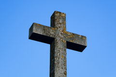 Stone Cross under Blue Sky. A old lichen-covered stone cross under a blue sky royalty free stock image