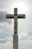 Stone crucifix with Jesus Christ before cloudy sky Stock Photo