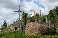 Stone with crucifixions near it Stock Images