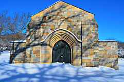 Stone Crypt in Snowy Cemetery. A beautiful stone, brick crypt in a snow covered cemetery in Lake Geneva, Wisconsin. There is neat shadows on the building from a stock images