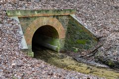 Stone culvert over the road for a small river. A small stream in a forest area stock photo
