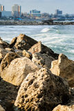 Stone dam agains the wavy sea and the city Royalty Free Stock Image