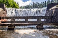 Stone dam creates a mountain waterfall Royalty Free Stock Photography