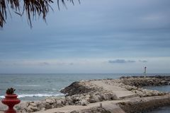 Stone dam with lighthouse and palm tree foreground. Pier on coast in the evening. Embankment on tropical seaside. Coastline in cloudy evening. Harbor landscape royalty free stock photos
