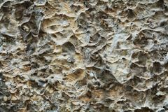 Stone decaying brown gray dark wall abstract background, craps and holes, abstract background royalty free stock images