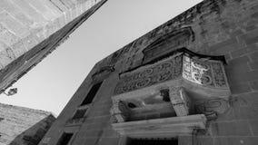 Stone Decorated Balcony in Citadel Victoria Gozo Malta. Dutch Angle black and white high contrast photography Stock Photo
