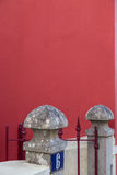 Stone decoration on pillar of fence on red wall Stock Image