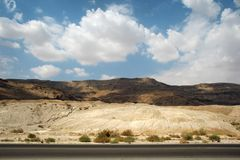 Stone desert and mountains along the road Royalty Free Stock Image
