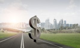 Money making and wealth concept presented by stone dollar symbol on asphalt road Royalty Free Stock Image