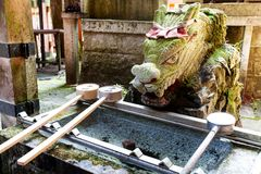 A stone dragon looks over a water trough for hand purification. Kyoto / Japan - 07/09/2017: Water for purification of hands, at Fushimi Inari Shrine Kyoto, Japan Stock Photography