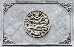 Stone dragon wall. Relief stone dragon on the wall Stock Images