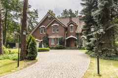 Stone driveway to house in english architectural style in the forest. Real photo stock image