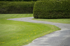 Stone Driveway. A winding stone driveway is shown next to a green lawn and cedar hedges in the eastern townships of Quebec Stock Photography