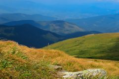 Stone in dry yellow grass on way to Hoverla on Carpathian mountains background, Ukraine. Horizontal outdoors shot royalty free stock image
