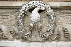 Stone eagle motif. An eagle with spread wings standing on a wreath, carved onto the facade of the great Georgian designer Sir John Soanes' villa in Ealing, West Stock Images