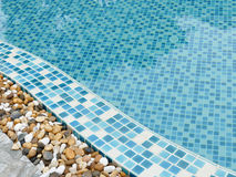 Stone on the edge of the swimming pool Stock Image