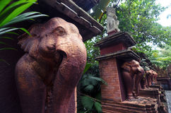 Stone elephant statues of bronze color in a sacred park Stock Photos