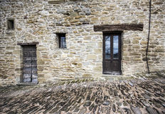 Stone façade and cobble street. Front view of a medieval stone façade house and cobble street stock photo