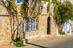 Stone facade with green ivy on silent street, Greece Royalty Free Stock Image