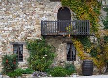 Stone facade of an old rural house with wooden balcony and ivy on it. Royalty Free Stock Images