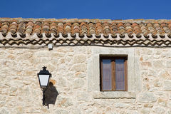Stone facade, window and lamp. Facade made of stone, window and lamp in a rustic house Stock Images