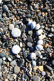 Stone face. A stone face on a pebble beach Royalty Free Stock Images