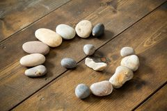 Stone face shape smiling made from pebbles. Happy smiling face made from beach pebbles on a wooden rustic table. Concepts for health, happiness, healing Stock Photography