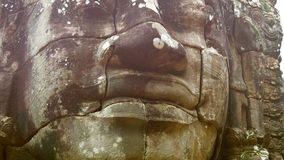 Stone face on the tower of the ancient temple. Bayon, Angkor, Cambodia