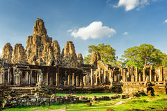 Stone faces of ancient Bayon temple. Angkor Thom, Cambodia. Mysterious ruins with stone faces of ancient Bayon temple in Angkor Thom in evening sun. Siem Reap Royalty Free Stock Image