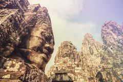 Stone faces on the towers of ancient Bayon Temple in Angkor Thom, Cambodia. Vintage color filter applied Stock Photography