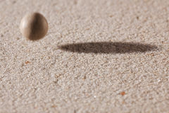 Stone falling down in sand Stock Photography