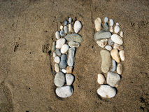Stone feet in the sand Royalty Free Stock Photo