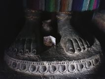 Stone feet standing on the pedestal of Buddha, feet with fingers, between the legs lies a donation, a banknote, a sculpture in a B Stock Images