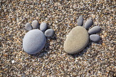 Stone feet. Two trace feet made of a pebble stone on the beach backdrop Stock Photo