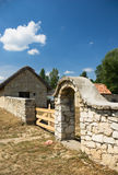 Stone fence. Old stone fence with a gate built of limestone Royalty Free Stock Photo