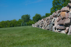 Stone Fence. A photo of a stone fence with green grass and a blue sky background Royalty Free Stock Photos