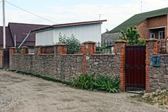 Stone fence and iron gates on a rural street Stock Images