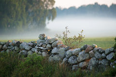 Stone fence with mist in the background.TN Stock Photo